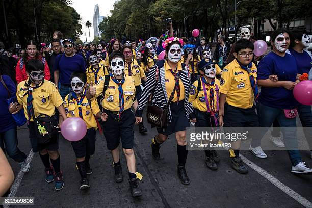 Children who wear a skeleton makeup parade through the streets during the 'Catrinas Parade' a joyful annual event celebrated at the Day of the Dead...