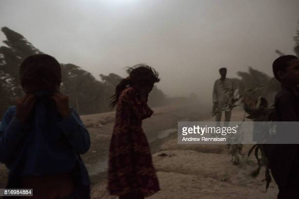 Children who were displaced by Islamic State of Iraq and Syria Khorasan hide their faces from a storm outside their current home on July 14 in Surkh...