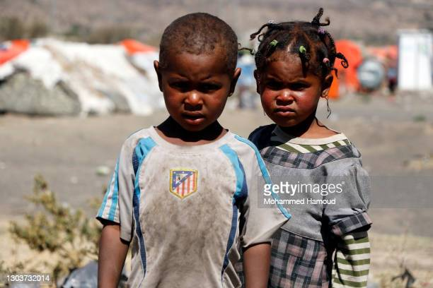 Children who were displaced due to the ongoing war stand beside tents at an internally displaced camp on February 21, 2021 on the outskirts of Sanaa,...