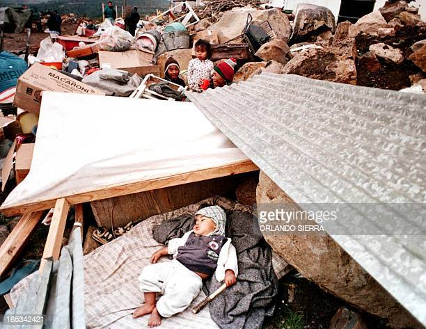 Children whose lives and families were affected by Hurricane Mitch sleep and play amid makeshift huts 28 November 1999 in the Honduran capital of...