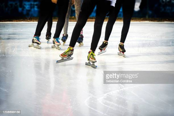 children, winter sport and leisure concept - close up of legs in speed skates on  skating rink, leader  in training lessons. - race leader athlete stock pictures, royalty-free photos & images