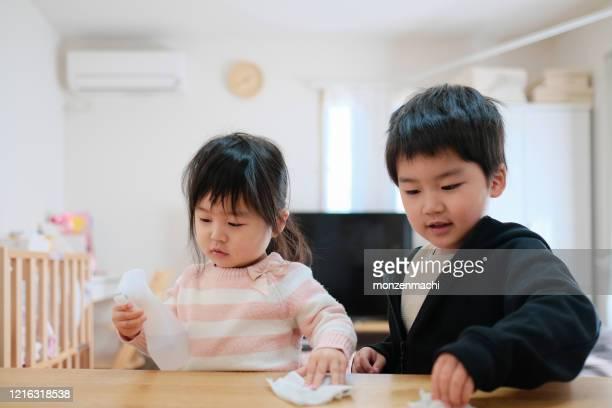 感染性ウイルスを防ぐためにテーブルの上で拭く子供たち - 掃く ストックフォトと画像