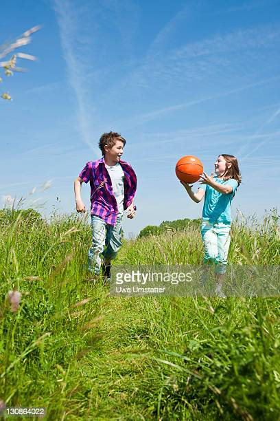 Children with a ball running through a meadow
