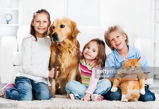 Kinder und Tiere sitzt auf dem Teppich.