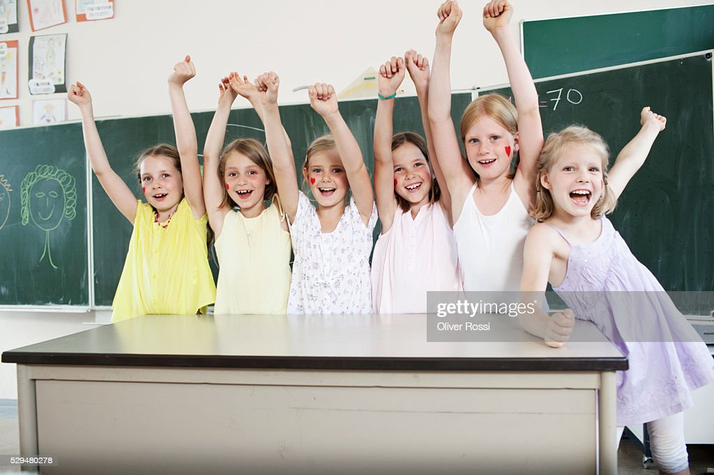 Children with arms raised in classroom : Stockfoto