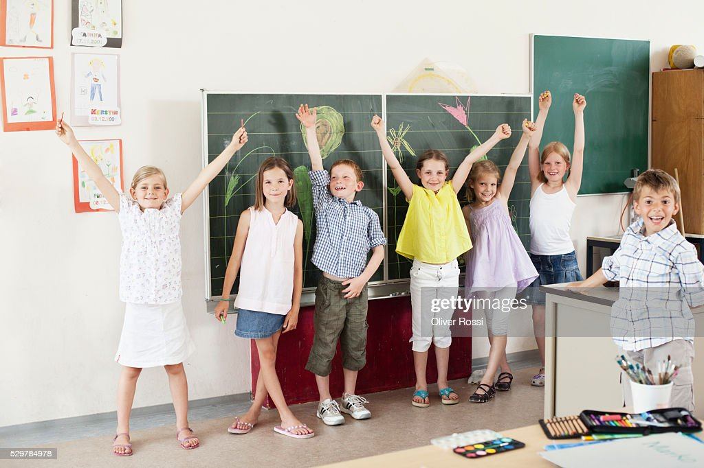 Children with arms raised in classroom : Stock-Foto