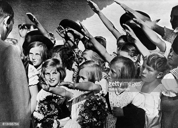 Children with bouquets greet the Nazi leader