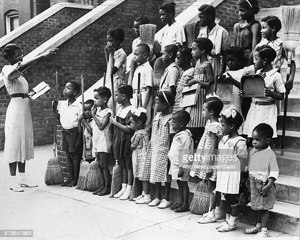Children with brooms during the Afro American Newspapers Clean Block campaign Baltimore Maryland 1939