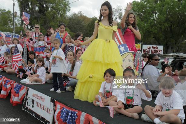Children with bunting on a float with bueaty queens for the parade at the Florida Strawberry Festival