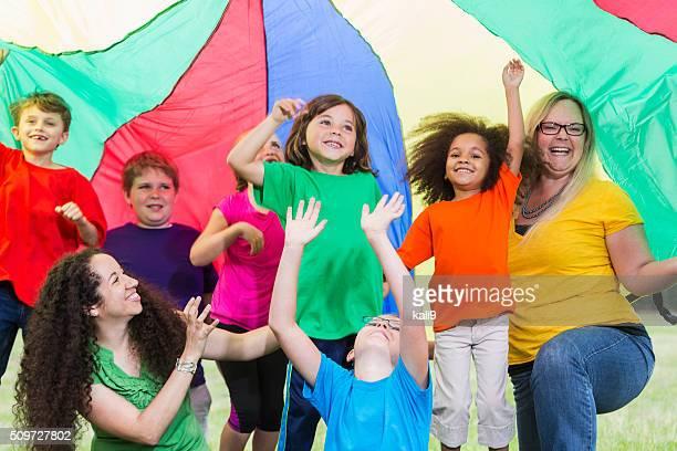 Betreuer im Kinder camp farbenfrohen parachute