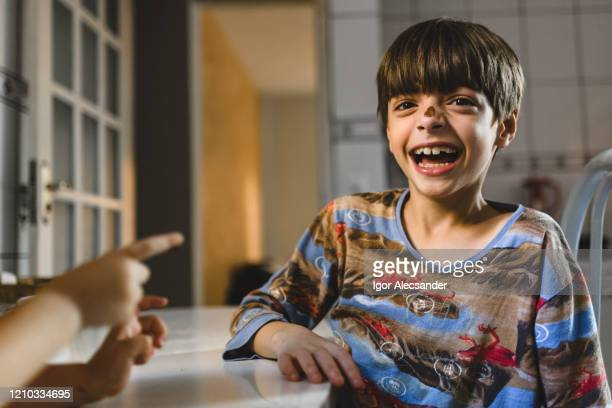 children with chocolate on the nose in the kitchen - easter sunday stock pictures, royalty-free photos & images