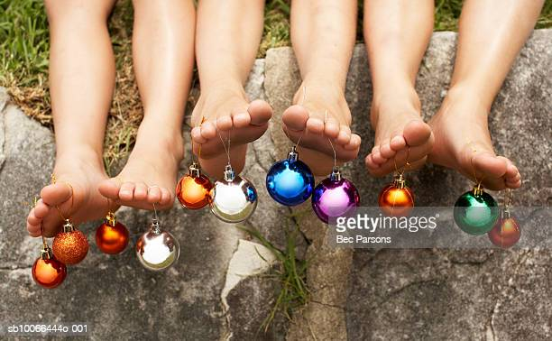 Children with Christmas baubles hanging from toes, low section