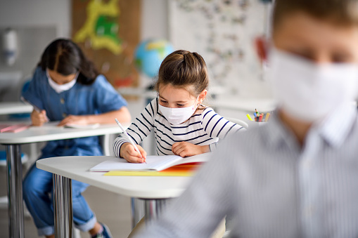 Children with face mask back at school after covid-19 quarantine and lockdown. 1250037717