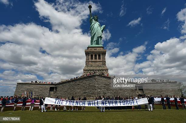 Children with flags stand in front of the Statue of Liberty on June 6 2014 on Liberty Island in New York Thousands gathered on the island to...