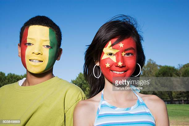 Children with Guinean and Chinese flags painted on faces