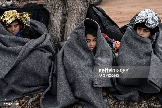TOPSHOT Children with life blankets sit on the beach after a dinghy with 54 Afghan refugees landed ashore the Greek island of Lesbos on February 28...