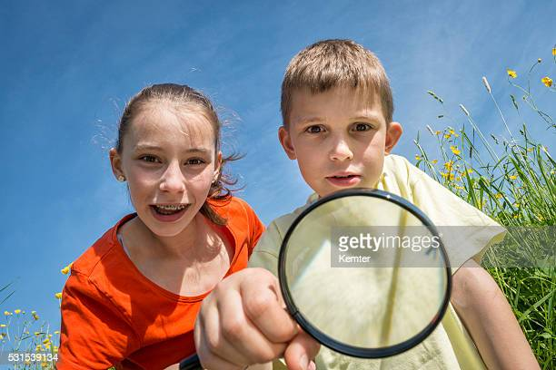 children with magnifying lens exploring the nature outdoors