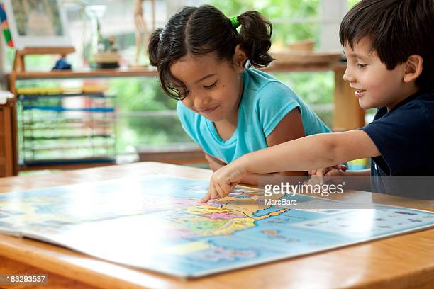 children with map book at school - physical geography stock pictures, royalty-free photos & images