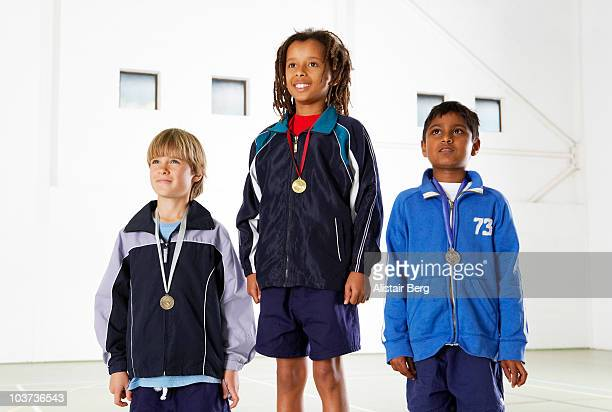 children with medals in gymnasium - winners podium stock pictures, royalty-free photos & images