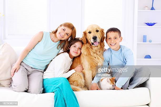 Children with mother and pets sitting on white sofa.