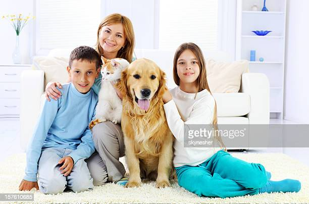 Children with mother and them cute pets sitting on carpet.