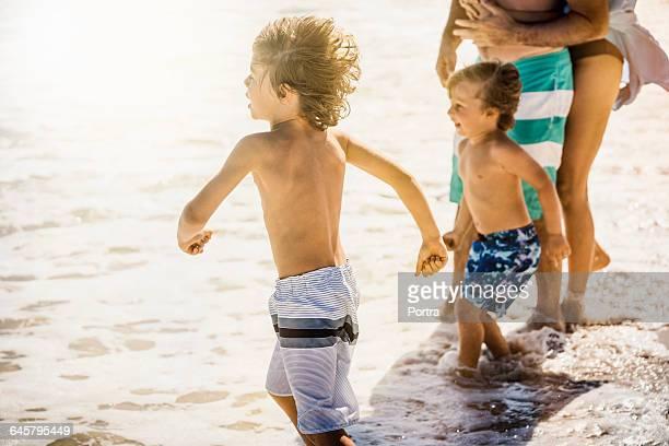 Children with parents enjoying on sea shore