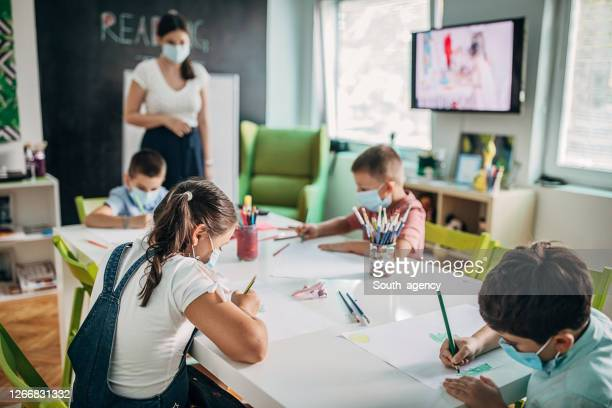 children with protective face masks drawing in preschool - nursery school child stock pictures, royalty-free photos & images