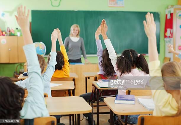 Enfants avec lever les mains dans une salle de classe
