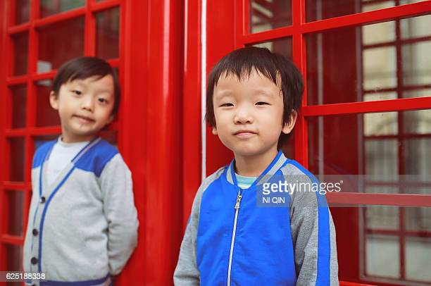 Children with red telephone box in the city