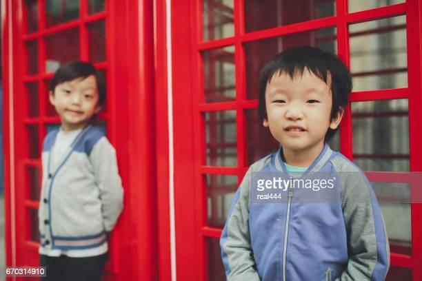 Enfants avec téléphone rouge boîte dans la ville