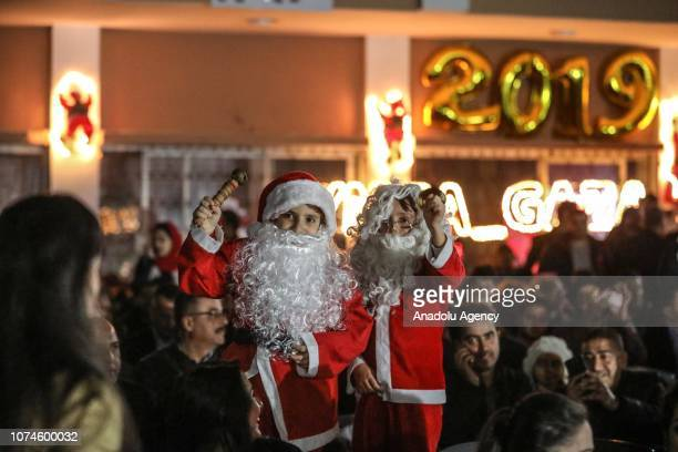 Children with Santa Claus costumes are seen as people gather around an illuminated christmas tree at yard of Christian Youth Association as part of...