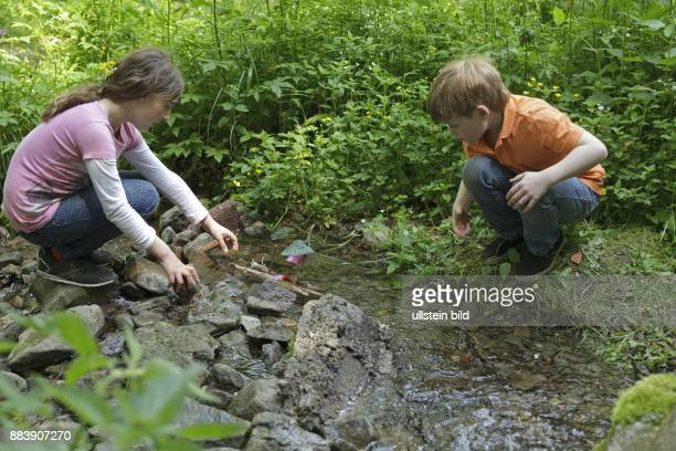 children with selfmade boats playing at a brook
