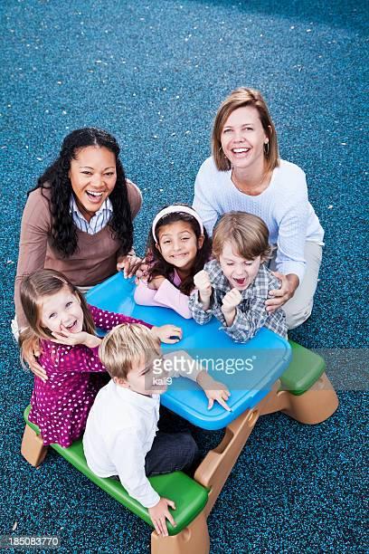 kinder mit lehrer in kindertagesstätten - mittelgroße personengruppe stock-fotos und bilder