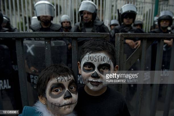 Children with their faces painted accompany their mother in a demonstration in front of the Mexican Electoral Tribunal building while inside a...