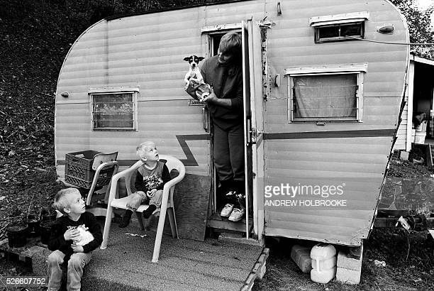 Children with their pet kitten and mother holding her Chihuahua at their mobile home