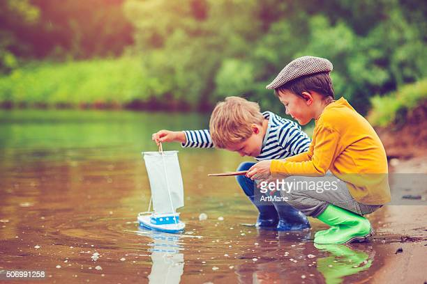 children with toy ship - spring flowing water stock pictures, royalty-free photos & images