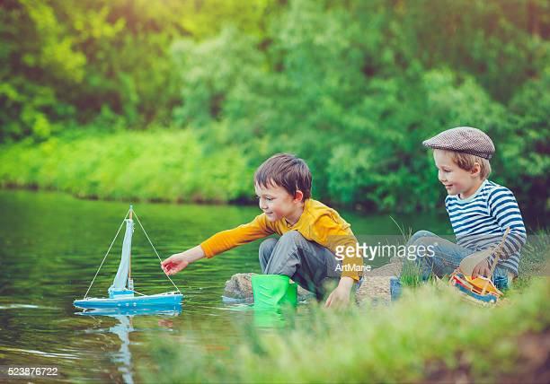 crianças com brinquedo navio - margem do rio - fotografias e filmes do acervo