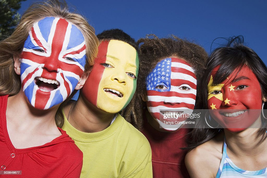Children with United Kingdom, Guinean, United States and Chinese flags painted on faces : Stock Photo