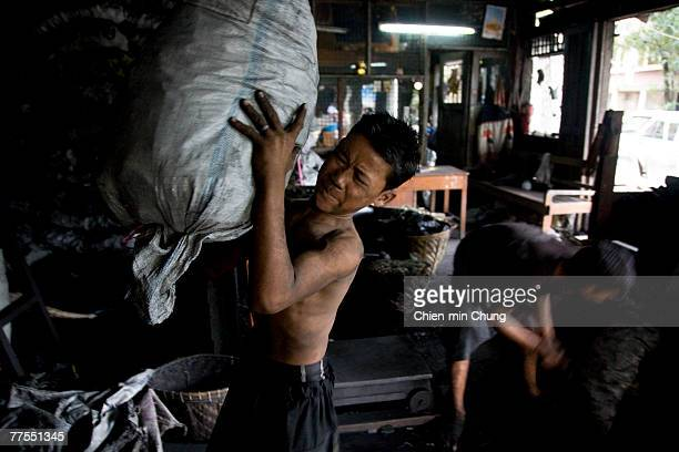 Children work in a charcoal store October 11 2007 in Rangoon Burma Despite international appeals for restraint in dealing with protesters the...