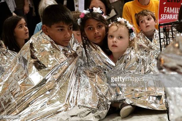 Children wrap themselves up with Mylar blankets to 'symbolically represent the thousands of children separated from families on the border sleeping...