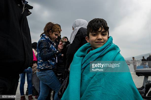 Children wrapped in a survival blanket looks on as migrants and refugees arrive on the Greek island of Lesbos while crossing the Aegean Sea from...