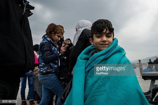 A Children wrapped in a survival blanket looks on as migrants and refugees arrive on the Greek island of Lesbos while crossing the Aegean Sea from...