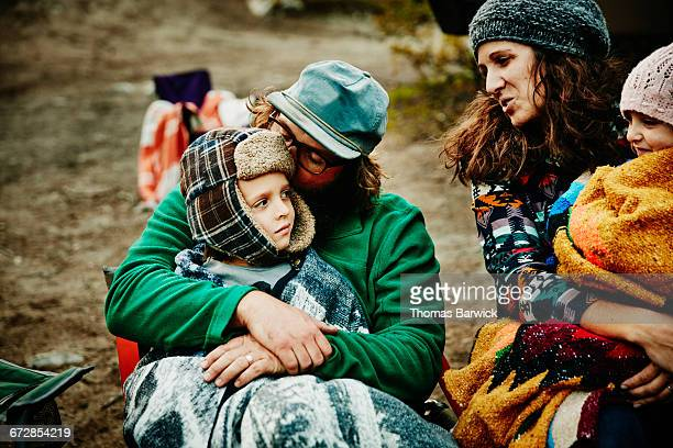 Children wrapped in blankets sitting with parents