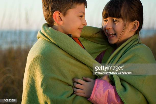 Children wrapped together in blanket outdoors, portrait