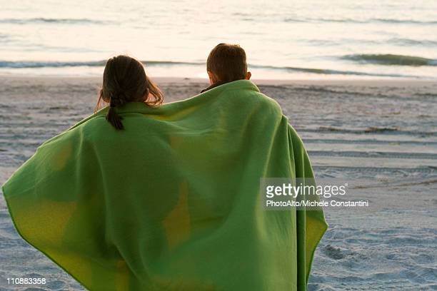 Children wrapped together in blanket standing on beach observing sunset
