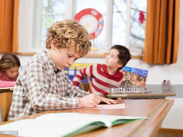 Children (4-7) writing exam in classroom, focus on boy