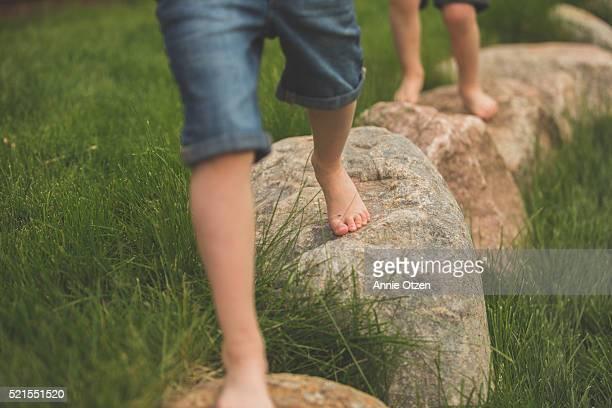 Children's bare feet walking on rocks