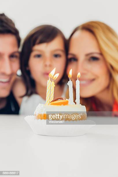 Childrens birthday with candles on cake and family in background