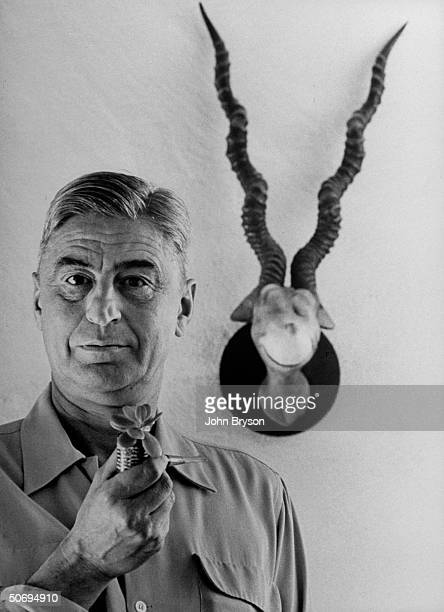 Children's book author Theodor Seuss Geisel holding favorite plantsprouting corncob pipe as he stands in front of his 1940 sculpture of the BlueGreen...
