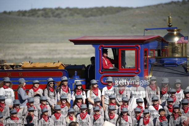 A children's choir stands on bleachers beside the steam locomotive Jupiter during a celebration of the 150th anniversary of the completion of the...